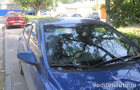 табличка с телефоном на лобовом стекле автомобиля